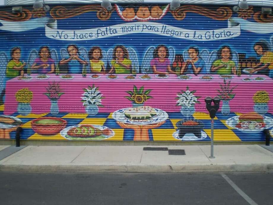 """Stephen Fries photo: The back of La Gloria restaurant is a mural by local artist Claudio Aguillon, depicting the love of family and food in Mexico and the U.S. """"You don't have to die to get to heaven"""" is the translation of the text in the banner."""