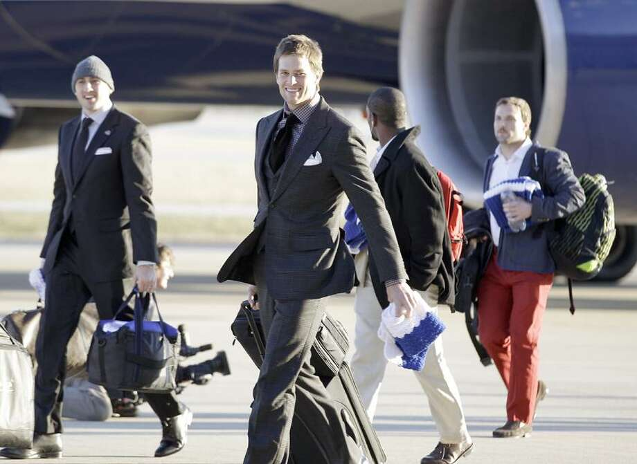 New England Patriots quarterback Tom Brady smiles as the team arrives at the Indianapolis International Airport for NFL footbal's Super Bowl XLVI Sunday, Jan. 29, 2012, in Indianapolis. (AP Photo/David J. Phillip) Photo: AP / AP2012