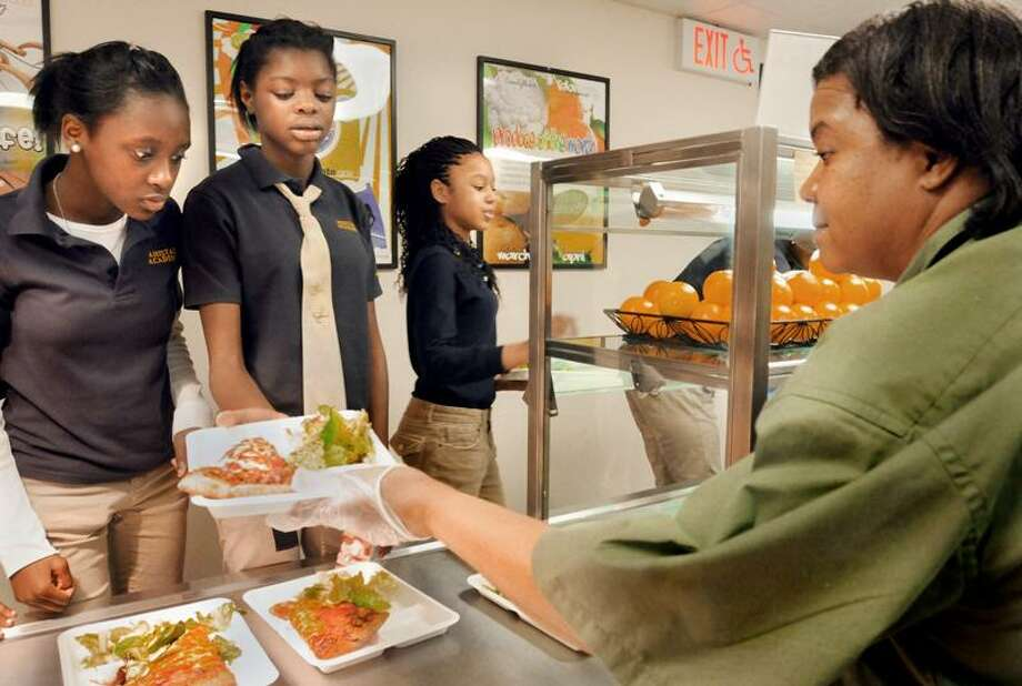 Ranice Caruth, left, and Danah Samuel, center, look over the pizza choices presented by Sharon Heyward as classmate Jasani Thompson takes her selection to the lunchroom.  Students had their choice of Cheese, pepperoni, or vegetable deluxe pizza.      Melanie Stengel/Register