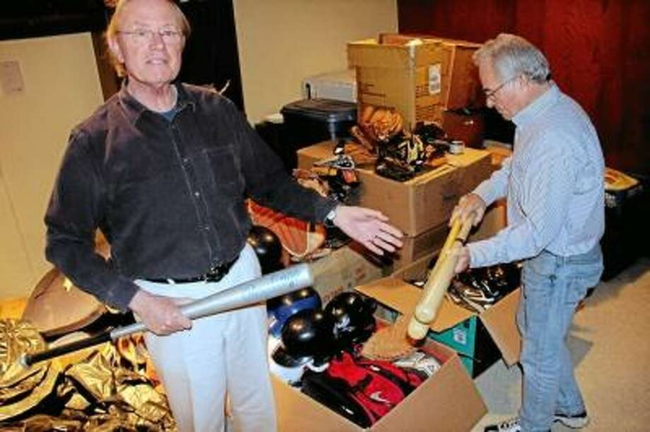 From left: Denis Horgan and Dick Foster browse through boxes of donated baseball gear - uniforms, cleats, gloves, bats, bases, and more - to be transported soon to Miami and then loaded onto a shipping container bound for Cuba. Kathleen Schassler/West Hartford News