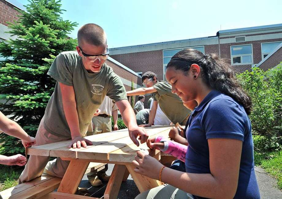 Freshman Carpentry student, Ray Witalis, left, from Emmett O'Brien Technical High School gives instruction to fourth-grader Janeliz Diaz as they sand benches at John G. Prendergast school. The three benches, which were constructed by the O'Brien students, will adorn the Prendergast courtyard.  Peter Casolino/New Haven Register