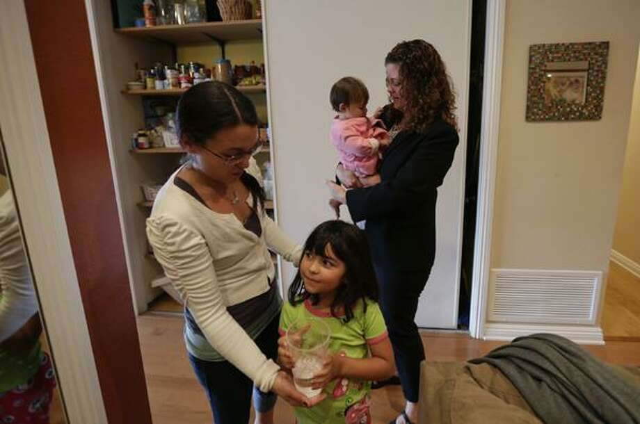 AP Photo Sabina Widmann, right, holds her baby girl Stella while domestic worker Alicia Wotherspoon, left, helps her daughter Luna with a glass of water before work at their home in San Diego. Photo: ASSOCIATED PRESS / AP2012