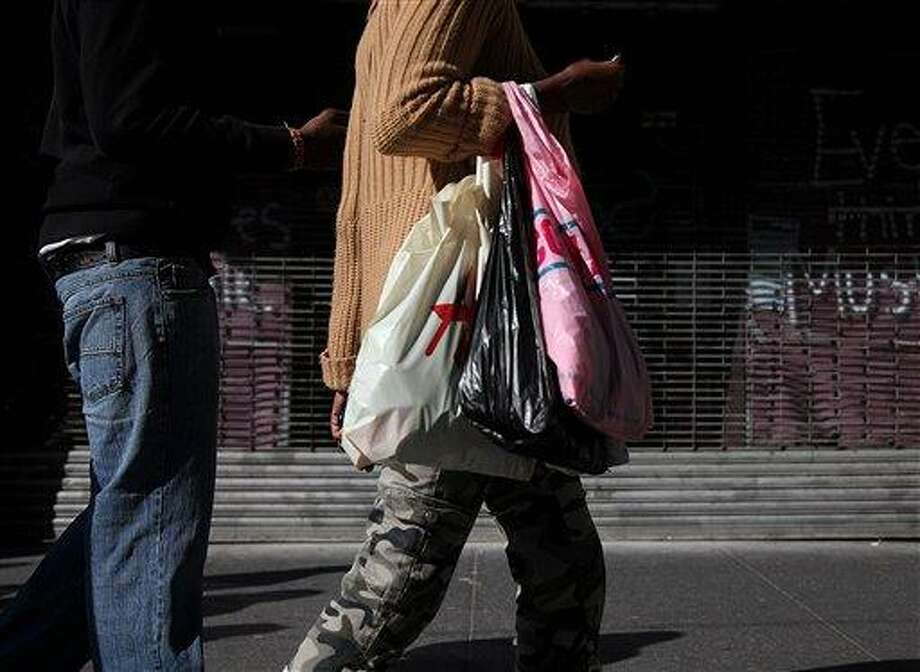 In this May 6 photo, shoppers carry their purchases along 33rd Street in New York. Americans' confidence in the economy in May had its biggest drop in eight months as consumers fretted about slow hiring, a big stock market drop and the global economy, according to the Conference Board, a private research group.  Associated Press Photo: AP / AP2012