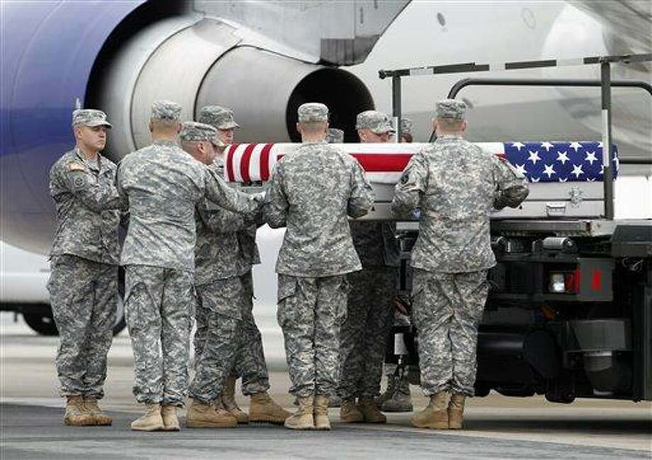 An Army carry team carries the transfer case containing the remains of Army Spc. Dennis P. Weichel Jr. of Providence, R.I., upon arrival at Dover Air Force Base, Del. The Department of Defense announced the death of Weichel Jr., who was supporting Operation Enduring Freedom in Afghanistan.  Associated Press Photo: AP / FR159526 AP