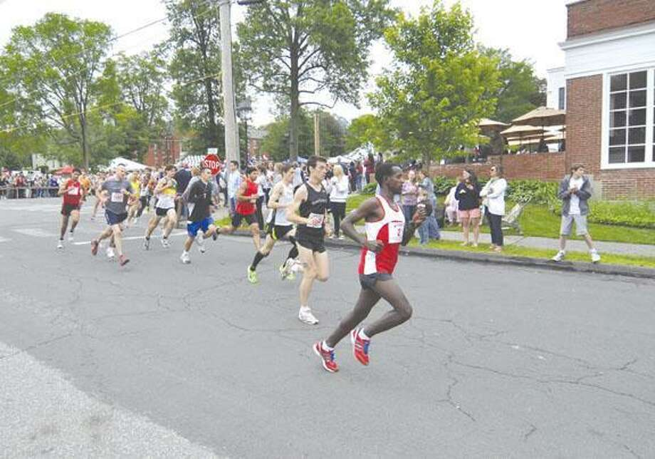 RICK THOMASON / Register Citizen Runners make the first turn in the 2011 Litchfield Hills Road Race. Eventual winner Mourad Marofit of Morocco is far left (red top, black shorts).