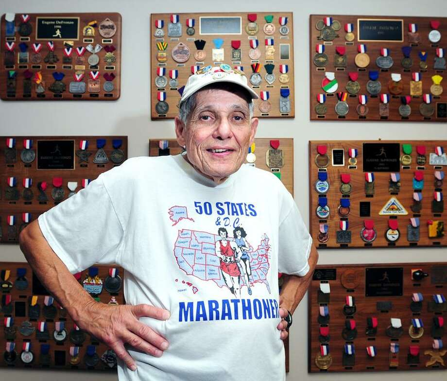 Eugene DeFronzo of Cheshire is photographed at his law office in Waterbury on 7/18/2012 in front of a wall full of medals from previous marathons.Photo by Arnold Gold/New Haven Register   AG0456E