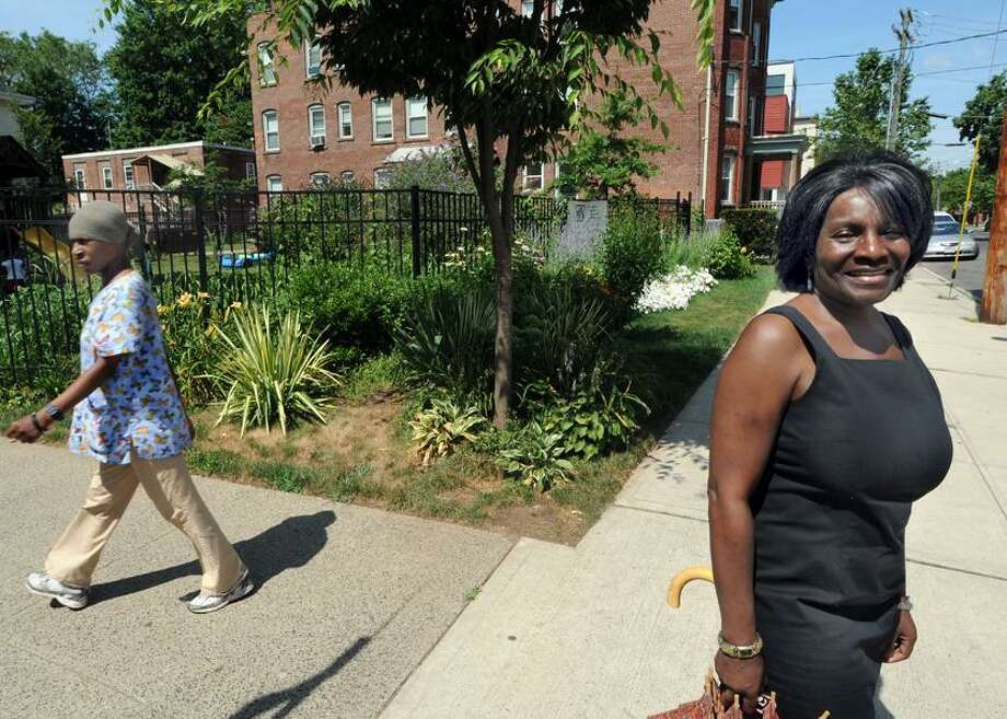 Linda Townsend Maier, executive director of the Greater Dwight Corp. stands near a Montessori School playground as well as a garden developed at the corner of Edgewood Ave. and Orchard St. by Greater Dwight for neighborhood improvements and beautification. Mara Lavitt/New Haven Register7/5/12