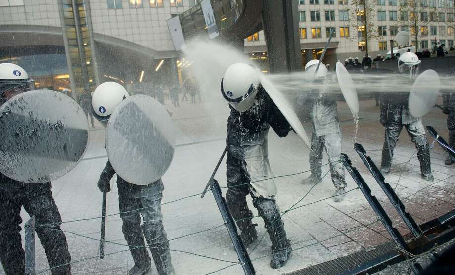 Police officers are sprayed with milk by European milk farmers during a demonstration outside the European Parliament in Brussels on Monday, Nov. 26, 2012. Farmers drove their tractors into the European Quarter of Brussels on Monday for a two-day demonstration to protest against what they believe are unfair milk prices. (AP Photo / Geert Vanden Wijngaert) Photo: ASSOCIATED PRESS / AP2012