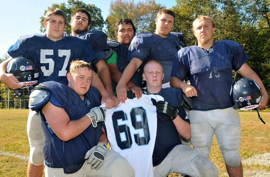 Linemen on the Oxford football team hold the No. 69 jersey of their fallen teammate, Brandon Giordano, who died in a car accident in March. They are, clockwise from bottom left, Liam Fay, Bucky Gumbrewicz, Justin Hanna, Fred Widmer, Dan Carbonaro, Josh Kupec and Kyle Sastrum. The Oxford lineman who best demonstrates hustle and determination during the week of practice gets to wear Giordano's jersey on game day. (Peter Casolino/Register)