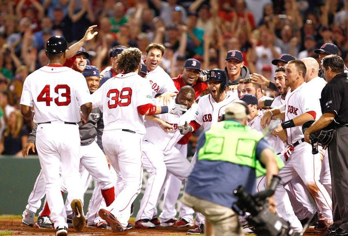 May 26, 2012; Boston, MA, USA; Boston Red Sox catcher Jarrod Saltalamacchia (39) is congratulated at home plate by his teammates after hitting the game-winning home run in the ninth inning against the Tampa Bay Rays at Fenway Park. Mandatory Credit: Mark L. Baer-US PRESSWIRE