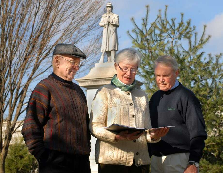 Left to right, Neil Hogan, Patricia Helsin, and George Waldron in front of the Ninth Regiment Monument in Bayeiew Park.    Melanie Stengel/Register