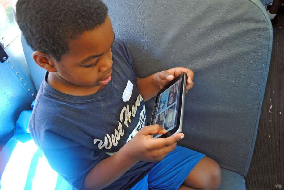 Isaiah Smith, 9, uses one of the tablets each student is given to continue practicing learning math and reading on the bus ride home from Summer Academy at Amistad Academy. It is a four-week program and the first of its kind in Achievement First network. Photo by Jen Fengler/for the Register