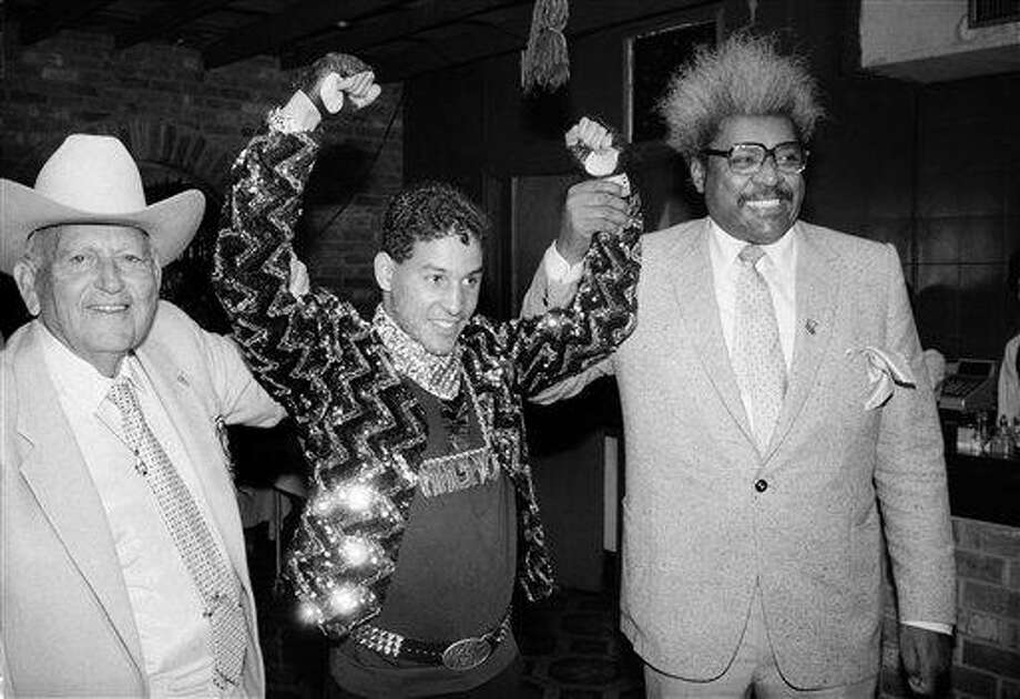 """FILE - In this Dec. 9, 1986 file photo, Hector """"Macho"""" Camacho WBC lightweight boxing champion, is escorted by Marty Cohen, left, and boxing promoter Don King, right, during a news conference in New York.  Famed Puerto Rican boxer Camacho is clinically brain dead, doctors said Thursday, Nov. 22, 2012, though they said family members were disagreeing on whether to take him off life support.  Dr. Ernesto Torres said doctors have finished performing all medical tests on Camacho, who was shot in the face Tuesday night. (AP Photo/David Bookstaver, File) Photo: AP / AP"""