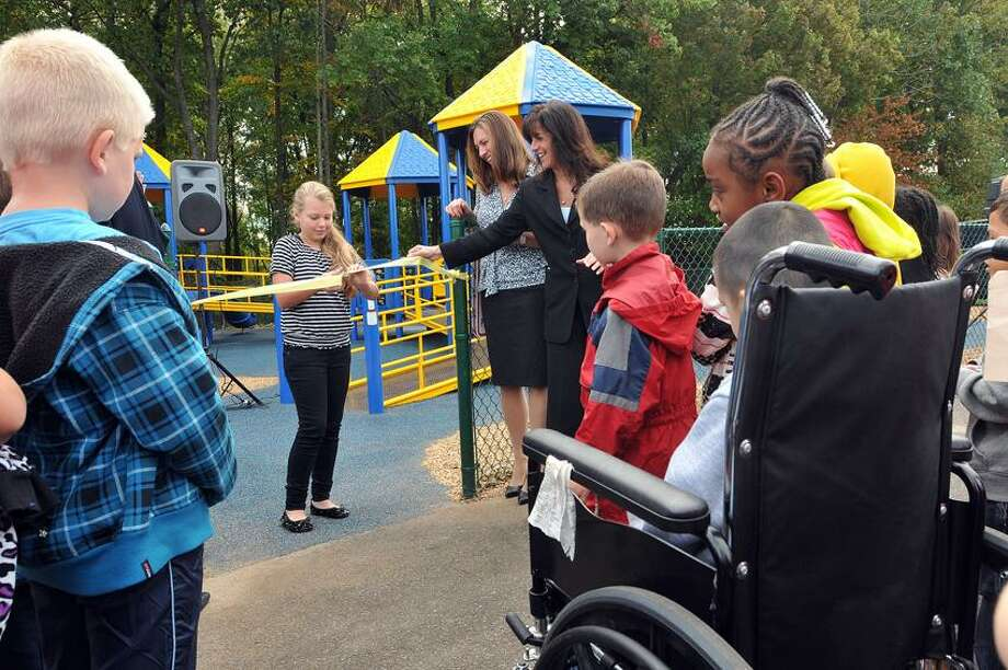 """Miranda Burrows, 11, cuts the ribbon on the new playground at Pagels School in West Haven. Burrows, whose question to her mother was the inspiration for the playground, after asking """"Why can't all kids play on the playground?"""" The new playground is wheelchair and handicapped accessible. Burrows attended Pagels in 4th grade. She is now a 6th-grader at Carrigan Intermediate School. Photo Peter Casolino/New Haven Register"""