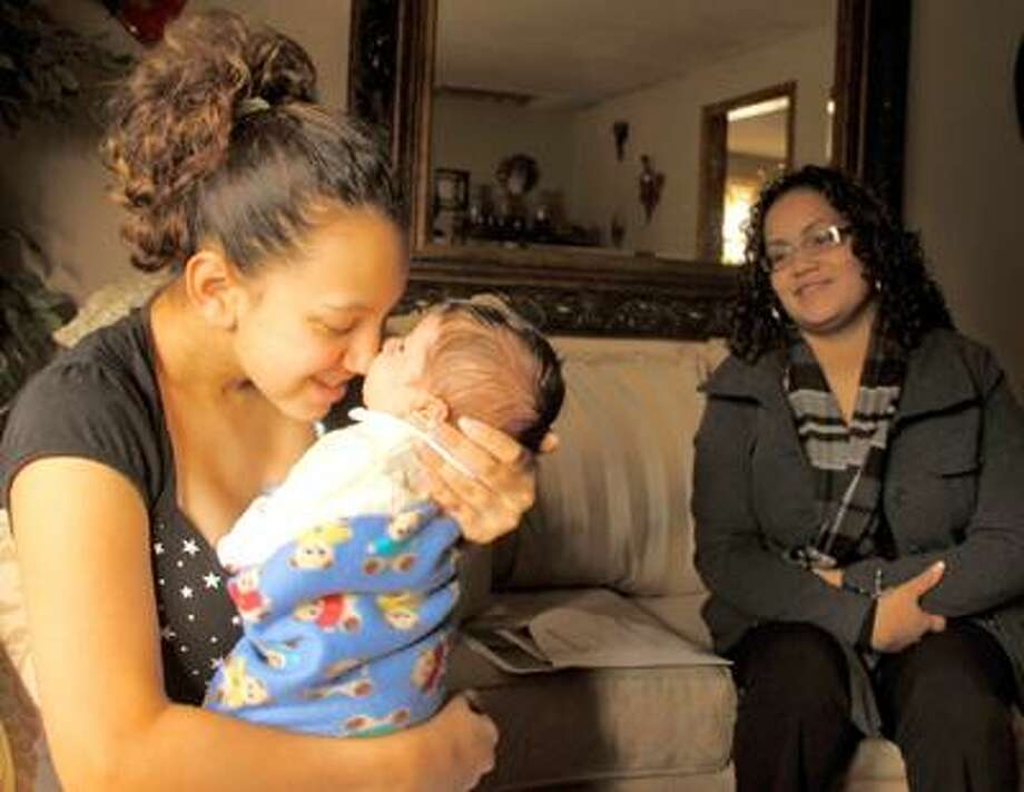 Tony Bacewicz I Special to the Press Yanisha Claudio, 15, cuddles her 1-month-old son, Jordan, during a home visit by Jennifer Colon of the Nurturing Families Network of Hartford. Colon is a home visitor who provides support and guidance to teen moms.