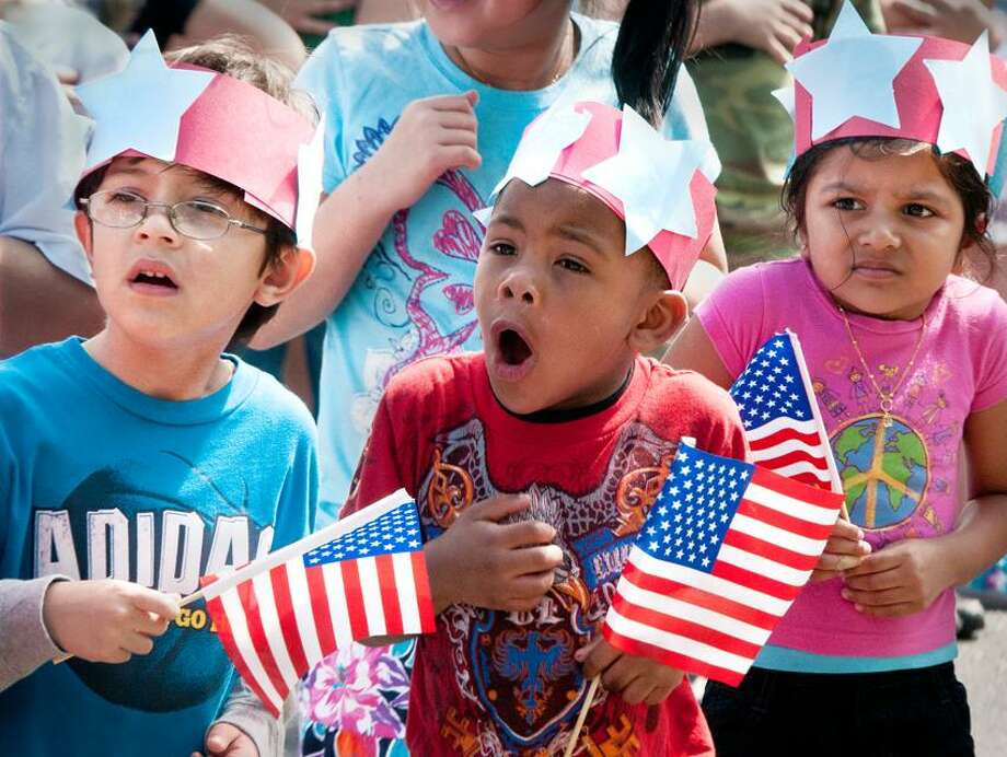 From left, Bradley Elementary School kindergartners, Sebastion Ramos, Kymere Wright, and Syna Patel react to salutatory shots fired by veterans during Memorial Day observances at the school.   Melanie Stengel/Register