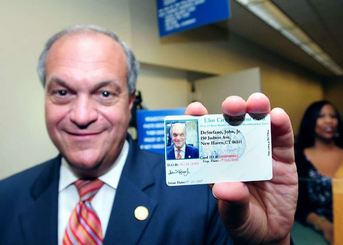 New Haven Mayor John DeStefano Jr., shows his new Elm City Resident Card after renewing the original card at the Office of Vital Statistics at New Haven City Hall. In the background at right is Lisa Wilson, director of Vital Statistics. Photo by Arnold Gold/New Haven Register