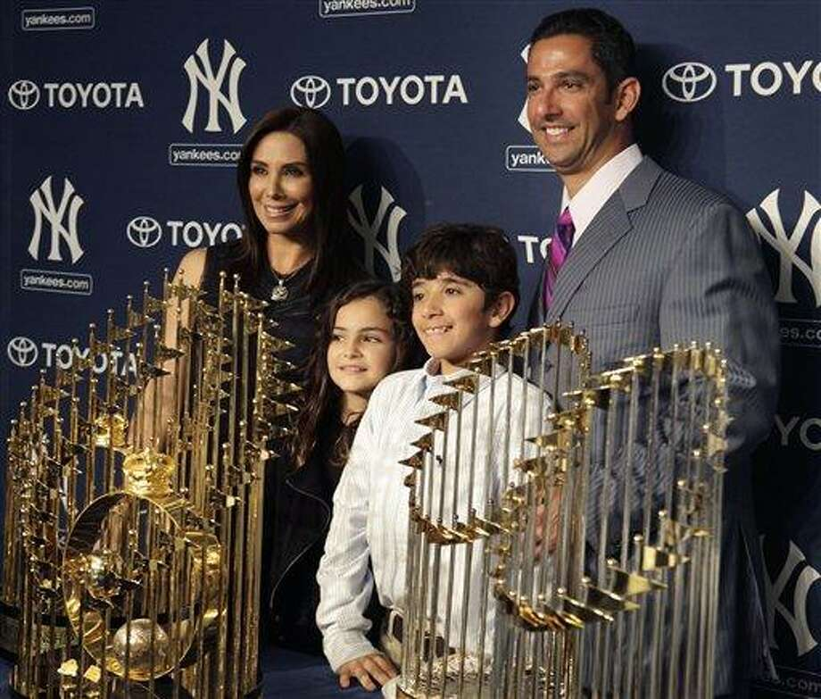 New York Yankees' Jorge Posada, right, poses for a picture with five World Series trophies and his family, wife Laura Posada, left, and children Paulina Posada, second from left, and Jorge Posda Jr. during a baseball news conference at Yankee Stadium in New York, Tuesday, Jan. 24, 2012.  Posada announced his retirement Tuesday. (AP Photo/Seth Wenig) Photo: AP / AP