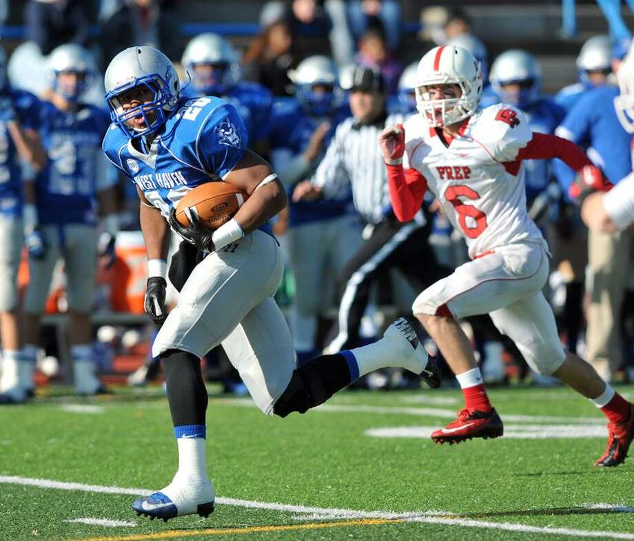 West Haven--West Haven's Eddy Williams blasts through Fairfield Prep's defense for the first TD of the game as David Geries gives chase during the first quarter.    Photo--Peter Casolino/New Haven Register