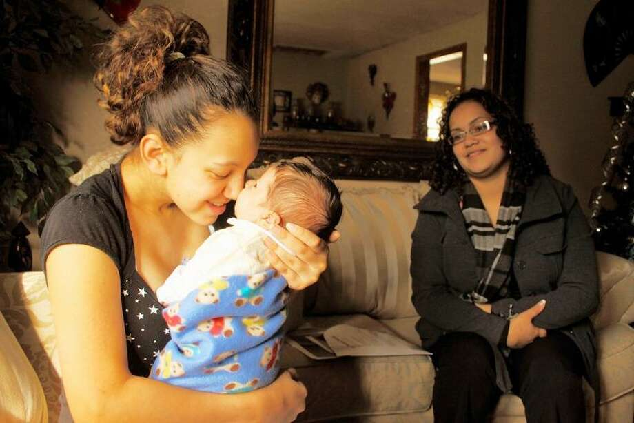Yanisha Claudio, 15, cuddles her 3-week-old son, Jordan, during a home visit by Jennifer Colon of the Nurturing Families Network of Hartford. Colon is a home visitor, who provides support and guidance to teen moms. Photo by Tony Bacewicz.