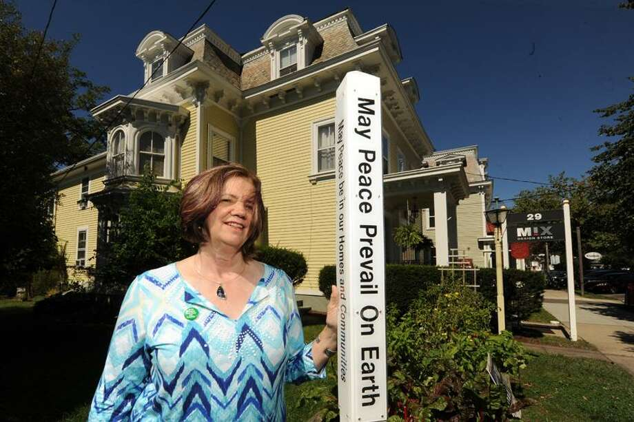 Kathryn Greene owner of Greene Art Gallery on Whitfield Street in Guilford stands next to a peace pole she erected. VM Williams/Register