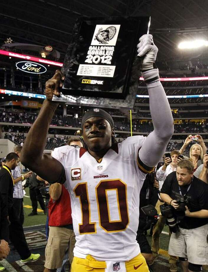 """Washington Redskins quarterback Robert Griffin III (10) holds up his """"Galloping Gobbler"""" award following a 38-31 win over the Dallas Cowboys in an NFL football game on Thursday, Nov. 22, 2012, in Arlington, Texas. (AP Photo/Tim Sharp) Photo: AP / AP2012"""