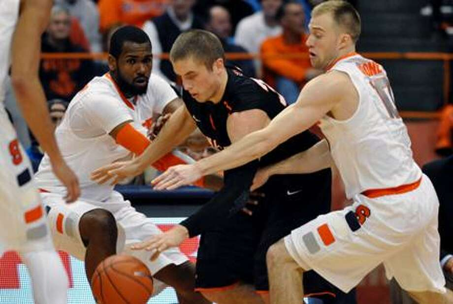Princeton's Ian Hummer, center, is pressured by Syracuse's James Southerland, left, and Trevor Cooney during the first half of an NCAA college basketball game, Wednesday, Nov. 21, 2012, in Syracuse, N.Y. (AP Photo/Kevin Rivoli) Photo: ASSOCIATED PRESS / AP2012