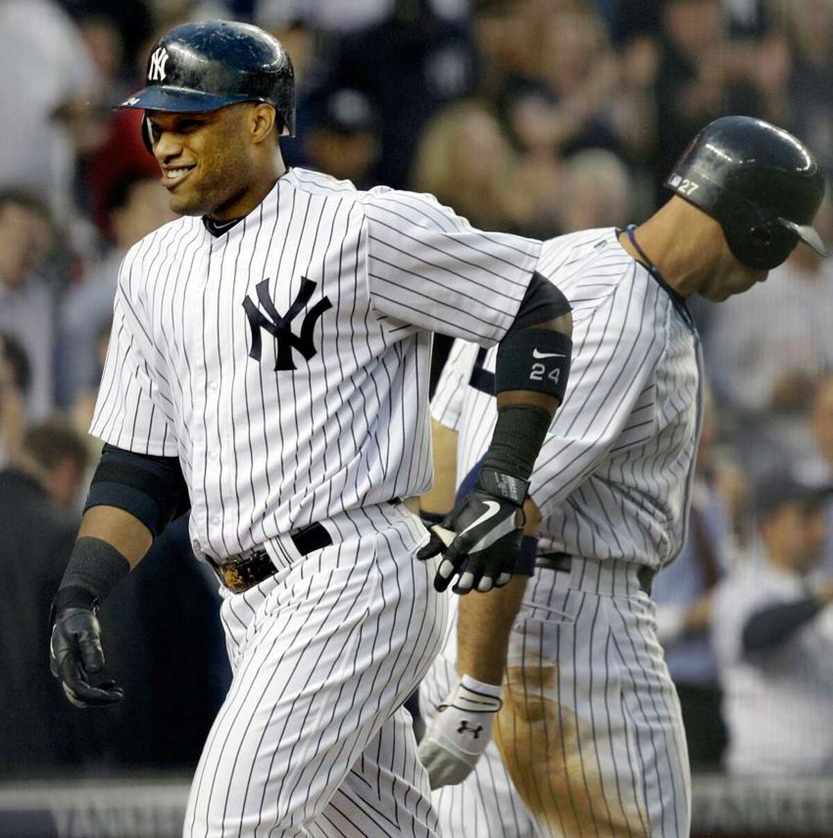 New York Yankees' Robinson Cano smiles heading to the dugout after hitting a solo home run during their baseball game in New York, Tuesday, May 22, 2012. The Yankees on-deck batter Raul Ibanez is at right. (AP Photo/Kathy Willens)