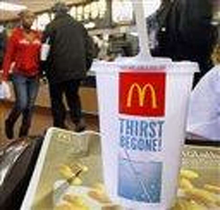 In this file photo, the McDonald's logo is displayed on a drink as customers purchase lunch at McDonald's, in Springfield, Ill. McDonald's Corp. saw net income jump 11 percent in the fourth quarter, as the fast-food giant continued to attract budget-conscious customers with low prices. Associated Press Photo: AP / AP