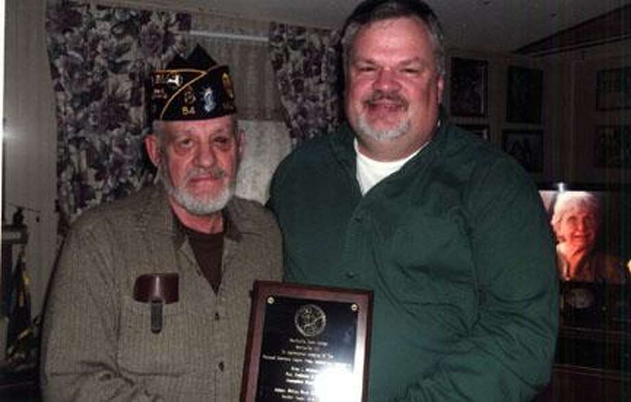 Submitted Photo Past President for the National American Legion Press Association Carl L. Griffith, left, presents a plaque to Brian L. McDowell, assistant professor and chair of the journalism department at Morrisville State College.