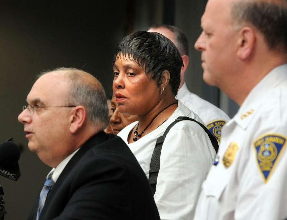 The New Haven Police Dept. held a press conference to announce the arrest of suspects in the murder of Donald Bradley on Whalley Avenue. Among those attending the press conference was Bradley's widow Louise center listening to Assistant Chief Archie Generoso left. At right is Police Chief Dean Esserman. Mara Lavitt/New Haven Register