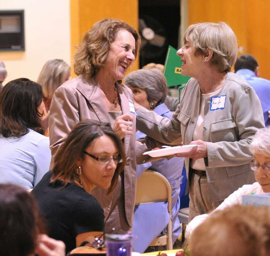 Donna Hersh, left, and Ruth Sachs share a laugh at the JCL's Volunteer Appreciation reception at the JCC. Hersh and Sachs are both volunteer readers at Davis Street School in New Haven. The woman seated in front of them, left, is Audrey Montesi, who is the literacy coach at Davis School.   Peter Casolino/New Haven Register