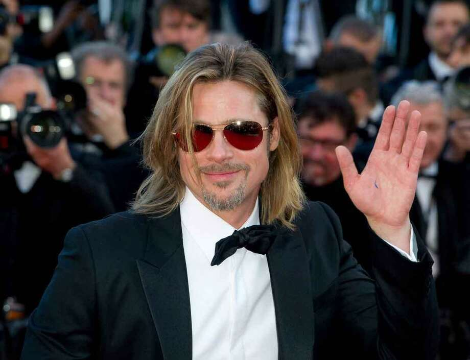 Actor Brad Pitt salutes the press as he arrives for the screening of Killing Them Softly at the 65th international film festival, in Cannes, southern France, Tuesday, May 22, 2012. (AP Photo/Jonathan Short) Photo: ASSOCIATED PRESS / AP2012