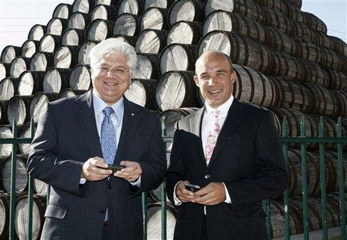In this July 14, 2009 file photo, BlackBerry maker Research in Motion's co-CEOs Jim Balsillie and Mike Lazaridis pose with their Blackberry devices before the RIM annual general meeting in Waterloo, Ontario. The company on Sunday says Balsillie and Lazaridis are stepping down, and will be replaced by Thorsten Heins, a chief operating officer who joined RIM four years ago from Siemens AG. Associated Press