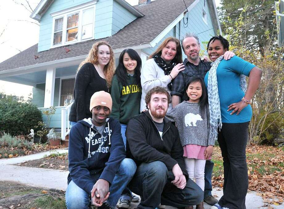 Hamden--The Morris family (Christel and Rob Morris, rear, second and third from right) with their children and their newly rehabilitated home. Left to right; Rear row, Amber (25), Michaela (16), Christel (Mom), Rob (Dad) and Jasmine (10). Front row, left to right; Micah (13), Tyler (23), Honour (7).    Photo (right) Peter Casolino/New Haven Register11/21/12