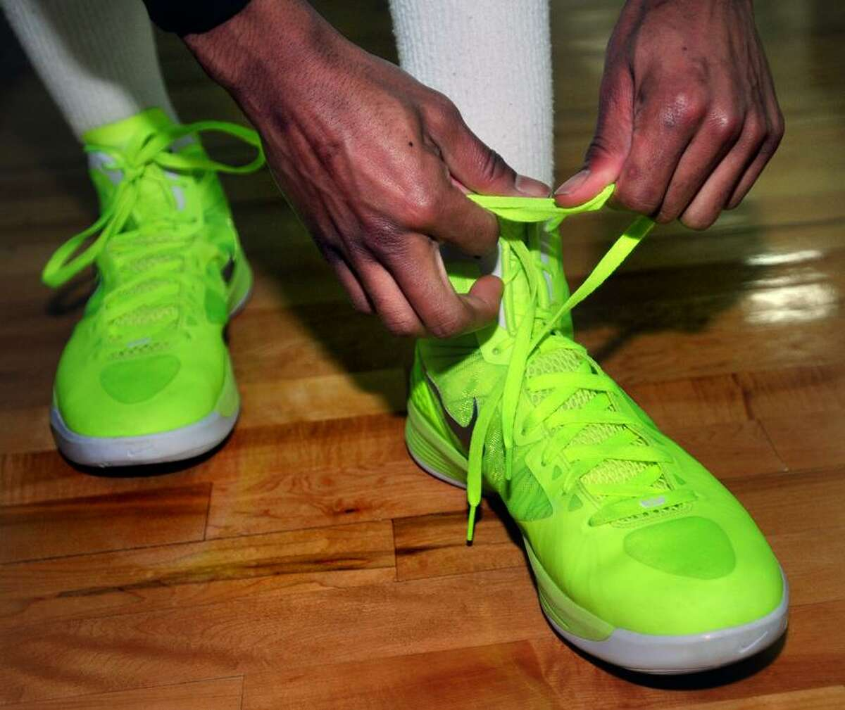 B.J. Davis of Hamden Hall laces his neon shoes for basketball practice at the Beckerman Athletic Center in Hamden on 1/20/2012.Photo by Arnold Gold/New Haven Register AG0436A