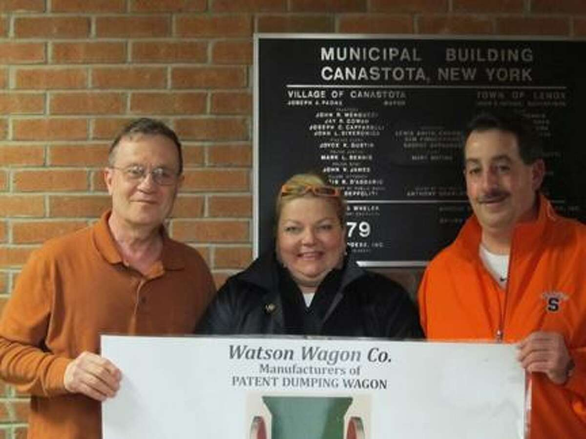 Submitted Photo Joe DiGiorgio, President of Canastota Canal Town, receiving a donation from Debra Golden and Vinnie Salamone of Basilio's Buda Sausage Co. for the Watson Wagon display building fund.