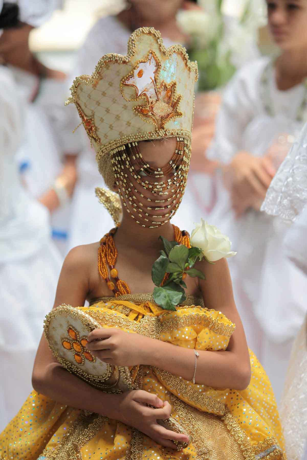 A girl dressed in ceremonial Oxun clothing takes part in a washing ceremony using lavender water during an event celebrating National Black Consciousness Day in Brasilia, Brazil, Tuesday, Nov. 20, 2012. National Black Consciousness Day honors African people's contribution to the history of Brazil and Oxun is a divinity from the African-Brazilian religion of Candoble representing the queen of all rivers and waterfalls. (AP Photo/Eraldo Peres)