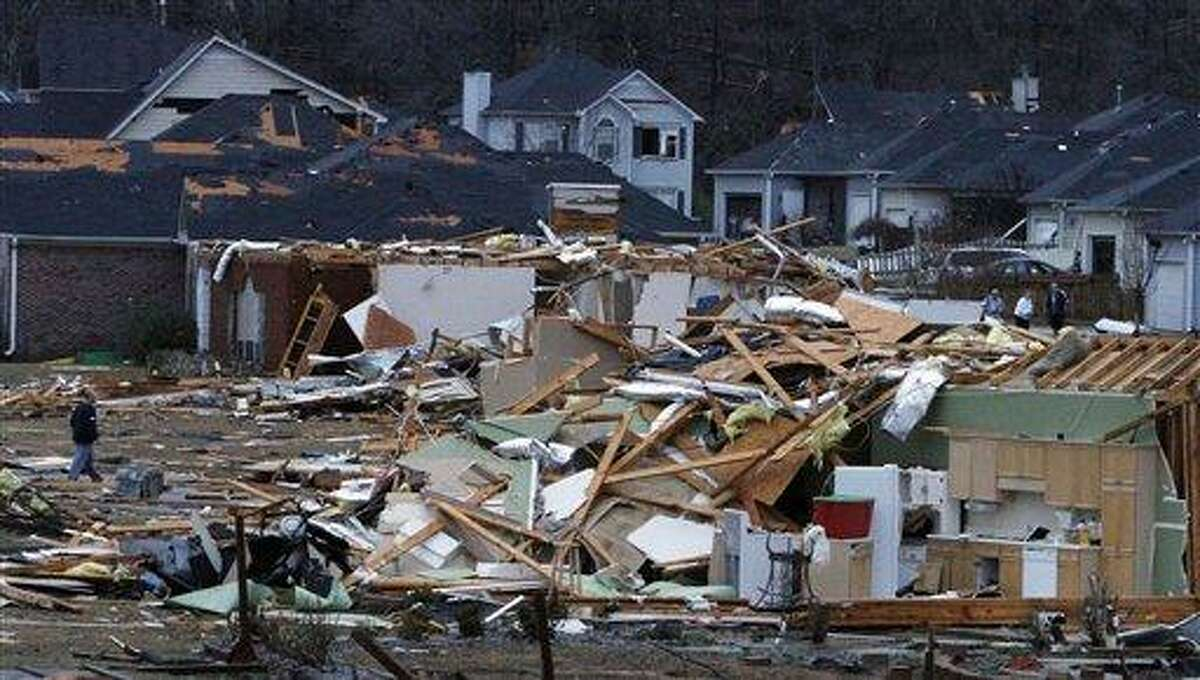 Residents walk around through the debris of their neighborhood after a possible tornado ripped through the Trussville, Ala. area in the early hours of Monday. Associated Press