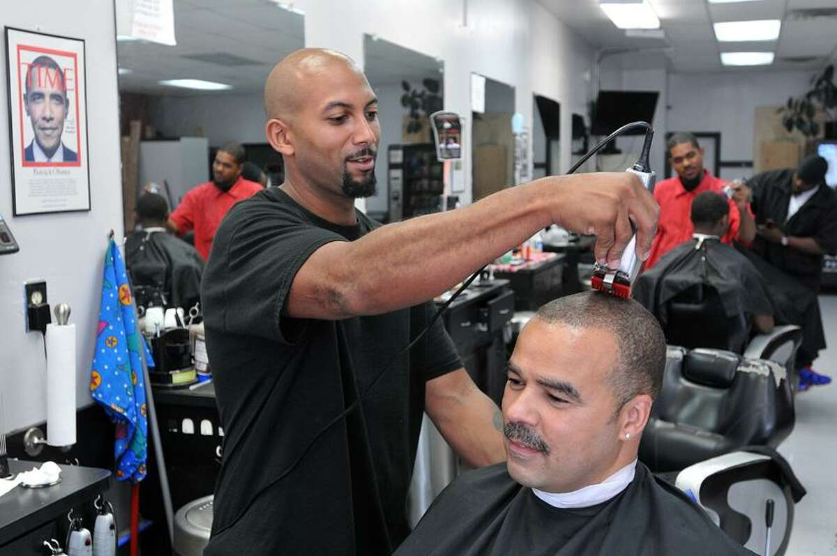 Michael Knight, owner of Knight's Extreme Barber Shop in Hamden, cuts Jeff Baskin's hair early Tuesday Afternoon. Baskin is a retired New Haven Fire Lt. Peter Casolino/New Haven Register