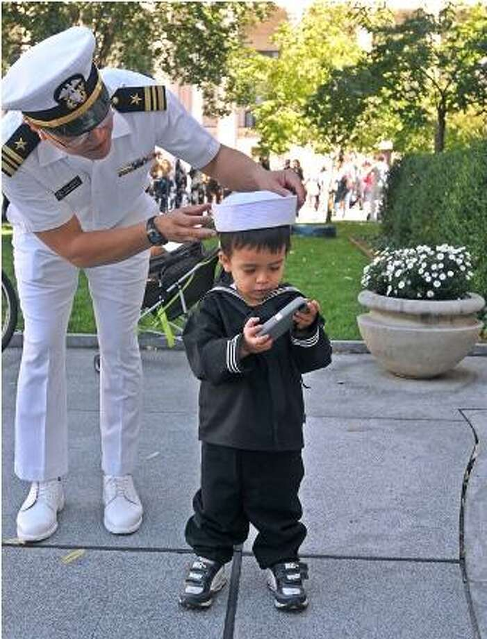 New Haven-- Retired Navy Lt. Commander Sylvester Salcedo adjusts his son, Leonardo's hat following the ceremony on Yale's Hewitt Quadrangle marking the return of the Air Force and Naval Reserve Officers Training Corps (ROTC) on the Yale campus. Salcedo is from Orange, and was at the ceremony to show support for the program. Leonardo is 2-years-old. Photo Peter Casolino/New Haven Register