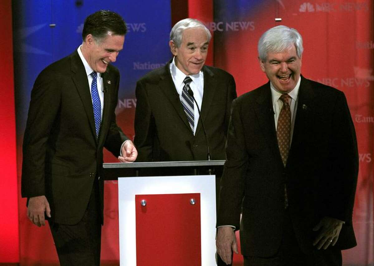 Republican presidential candidate, Rep. Ron Paul, R-Texas, center, shares a joke with former Massachusetts Gov. Mitt Romney, left, and former House speaker Newt Gingrich, right, during a break in a Republican presidential debate Monday at the University of South Florida in Tampa, Fla. Associated Press