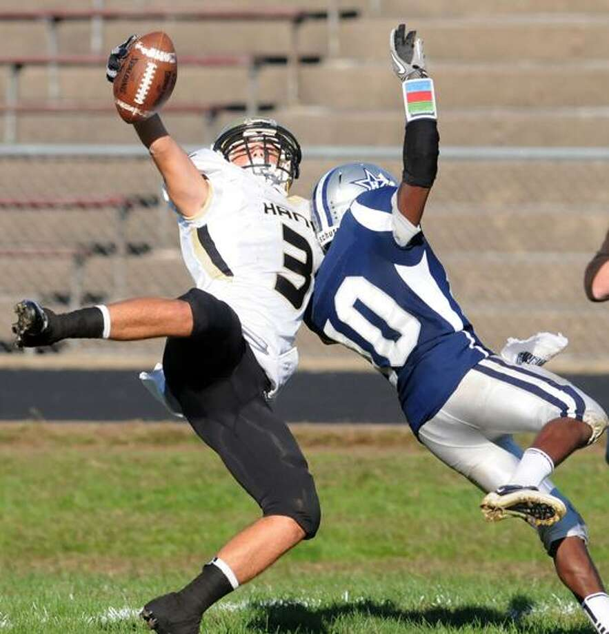 Hand's Jason Raleigh reaches up for the pass but collides with Hillhouse's Je'Vaughn Moore. Mara Lavitt/New Haven Register