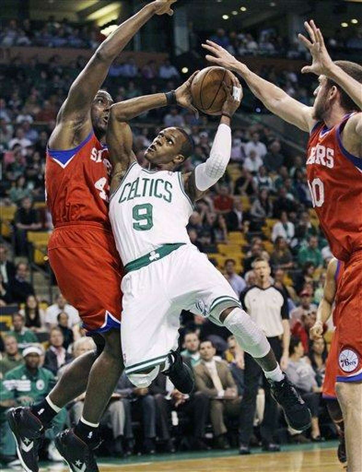 Boston Celtics guard Rajon Rondo (9) is double teamed by Philadelphia 76ers defenders Elton Brand, left, and Spencer Hawes on a drive to the basket during the first quarter of Game 5 in their NBA basketball Eastern Conference semifinal playoff series in Boston, Monday, May 21, 2012. (AP Photo/Charles Krupa)
