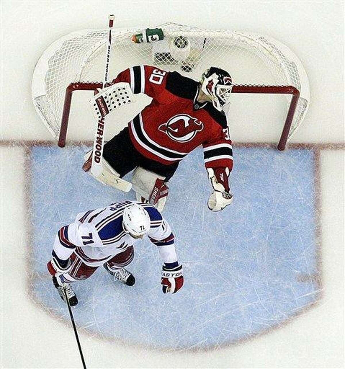 New Jersey Devils goalie Martin Brodeur, top, reacts after being punched by New York Rangers' Mike Rupp, center, during the third period of Game 4 of an NHL hockey Stanley Cup Eastern Conference final playoff series, Monday, May 21, 2012, in Newark, N.J. The Devils won 4-1. (AP Photo/Julio Cortez)