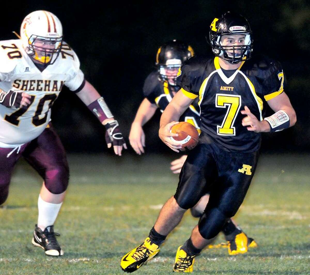 Amity quarterback James Semmonella, right, finds a big hole in the first half against Sheehan. Amity won 58-14. Photo by Arnold Gold/New Haven Register