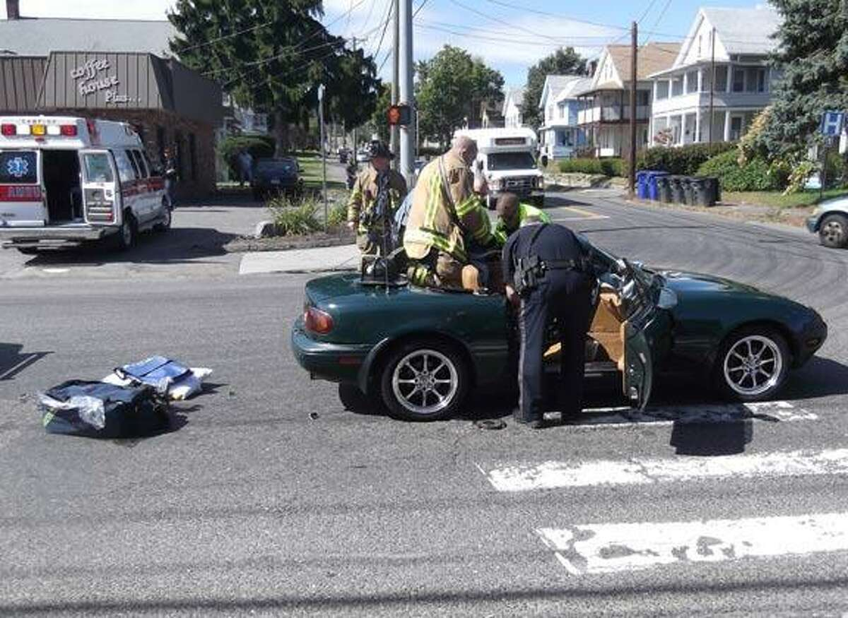 Rescue workers take a victim out of her car after an alleged hit-and-run accident Friday morning in Torrington.Photo by Sarah Bogues/Register Citizen Staff.