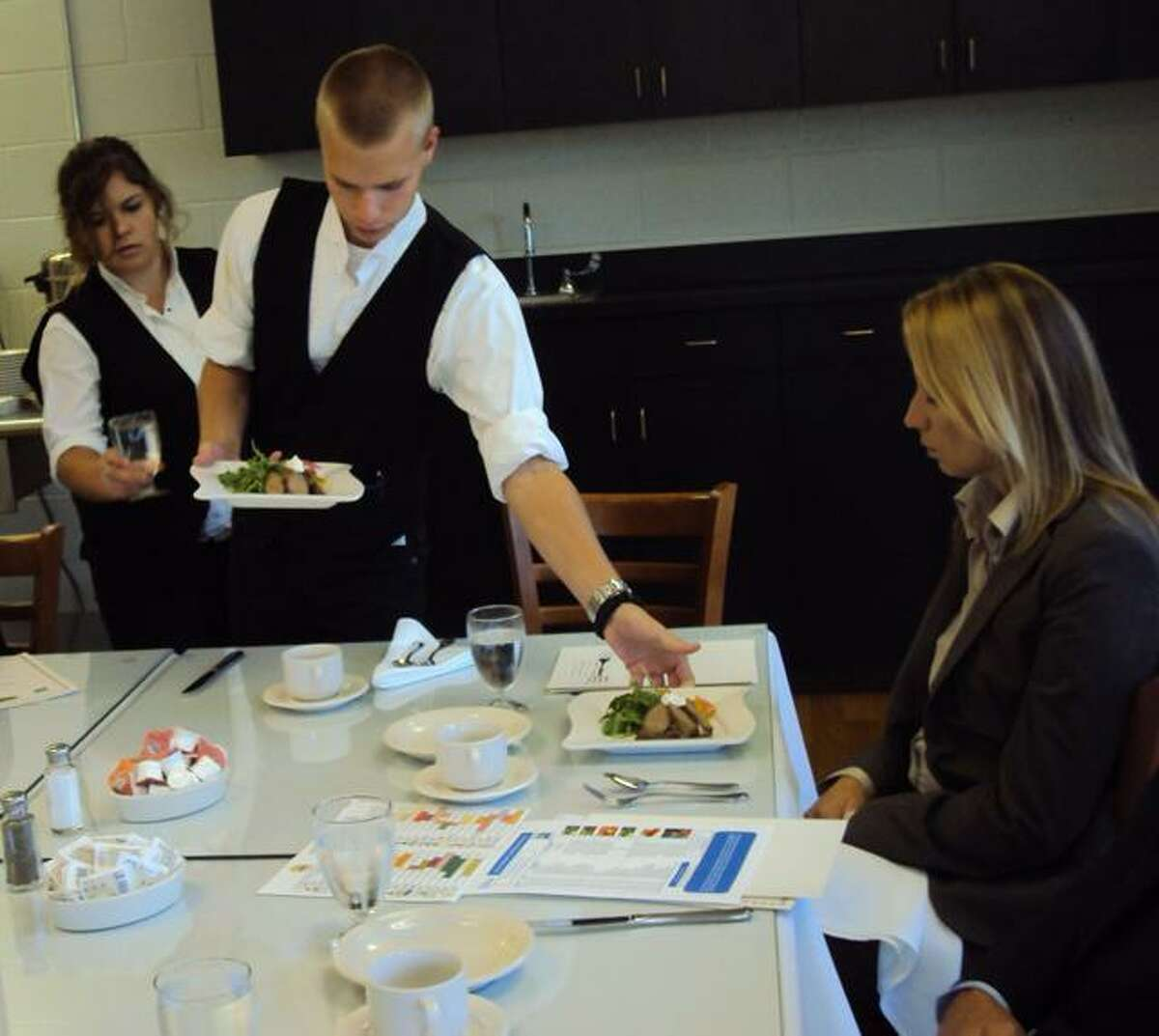 An Oliver Wolcott student serves Rep. Michelle Cook a dish as part of Farm-to-Chef Week 2012.