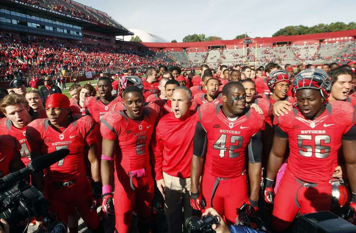 Rutgers head coach Kyle Flood, center, stands with his players as they sing Rutgers' almamMater after defeating Syracuse 23- 15 at home on Oct. 13. Rutgers is announcing that it will join the Big Ten.