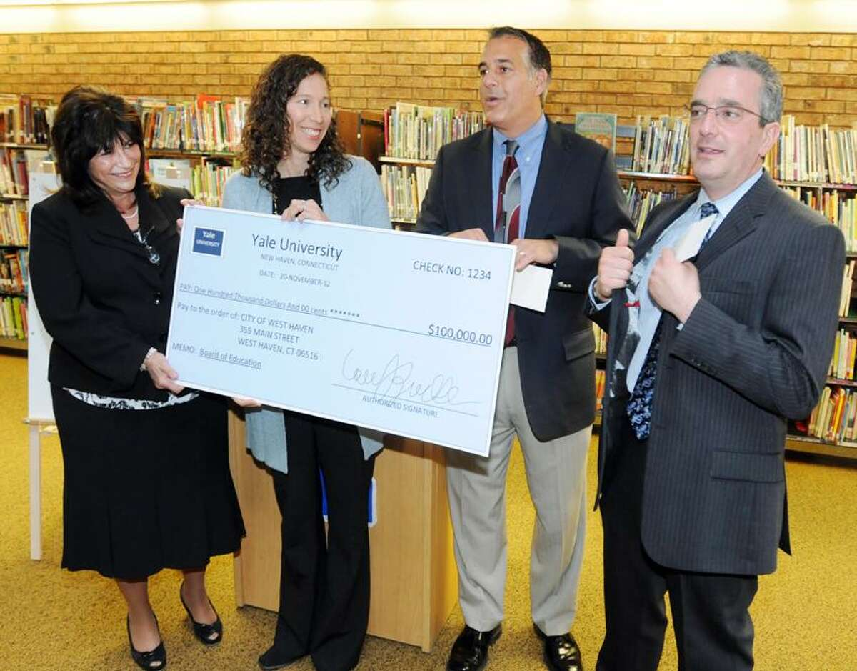 From left: West Haven Assistant Superintendent of Schools Anne P. Druzolowski watches as Lauren J. Zucker, associate vice president and Director of New Haven Affairs, presents a $100,000 mock check for the school system's early literacy initiative to West Haven Mayor John Picard as West Haven Superintendent Neil C. Cavallaro pockets the real check during a formal presentation Tuesday, November 20, 2012 at the Savin Rock Community Center in West Haven Photo by Peter Hvizdak / New Haven Register